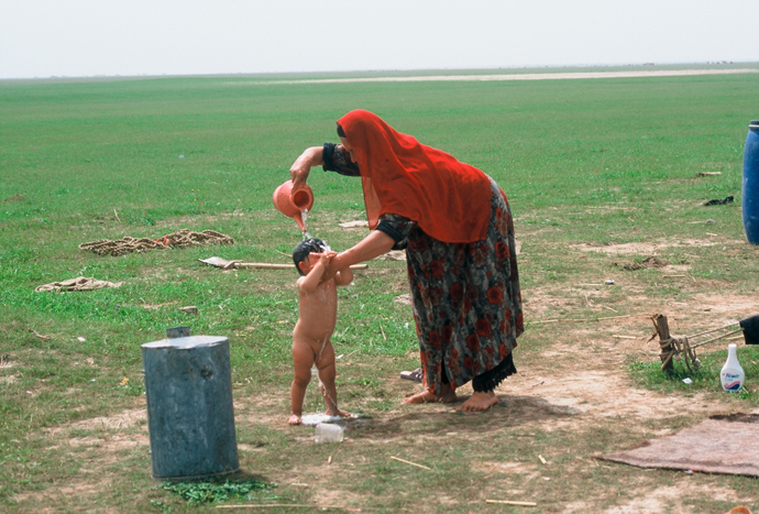 <p>Fig. 12: A woman in Kunduz Province bathes her child in water from a stream. <br />Sheryl B. Shapiro, 2003</p>