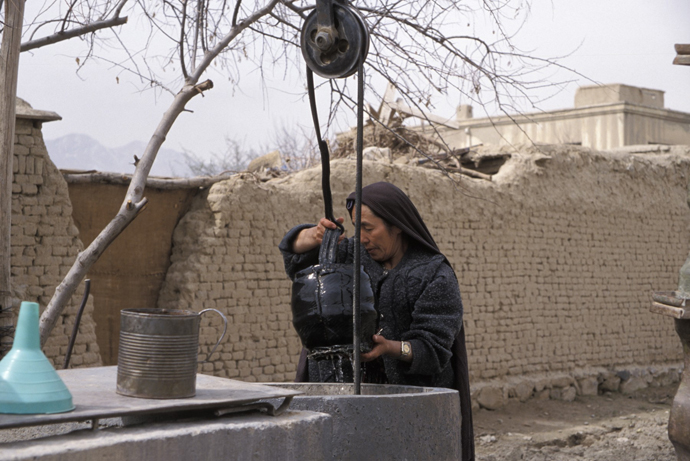 <p>Fig 13: A widow draws water from a well in her small back yard outside Kabul. She is part of the PARSA (Physiotherapy and Rehabilitation Support for Afghanistan) Widow&rsquo;s Garden Program founded by Mary MacMakin and conceived by Zarguna Hashimi, PARSA&rsquo;s former director of Literacy and Early Childhood Development Service, who lost her husband during the Soviet War. The program serves twenty widows. <br />Photo by Sheryl B. Shapiro, 2003.</p>
