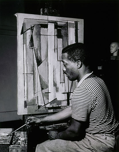 <p>Norman Lewis working on <em>Composition I,</em> 1945 <br />Courtesy of Willard Gallery Archives</p>
