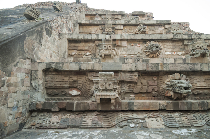 <p>View of the facade of the Feathered Serpent Pyramid, assembled as a mosaic of large and small sculptures. The head of the Feathered Serpent juts out from the tablero. Its body wraps around the building and carries a headdress thought to represent a primordial crocodile, or the so-called War Serpent. The shells surrounding the Feathered Serpent emphasize that the building represents a watery location, like a mountain rising from the sea. Photograph by Jorge P&eacute;rez de Lara El&iacute;as, &copy; INAH <br /><br />Image courtesy of the Fine Arts Museums of San Francisco</p>